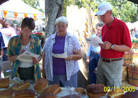 Our judges taste and view the loaves of bread for the contest. Click the photo to see a closer view.